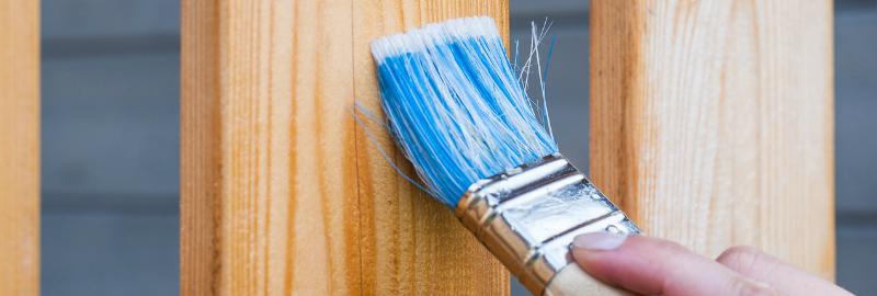 une personne peint son bois extérieur